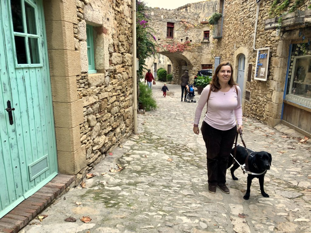 A woman accompanied by a guide dog walks down a cobbled street at Peratallada. Image by Isabel Godoy.