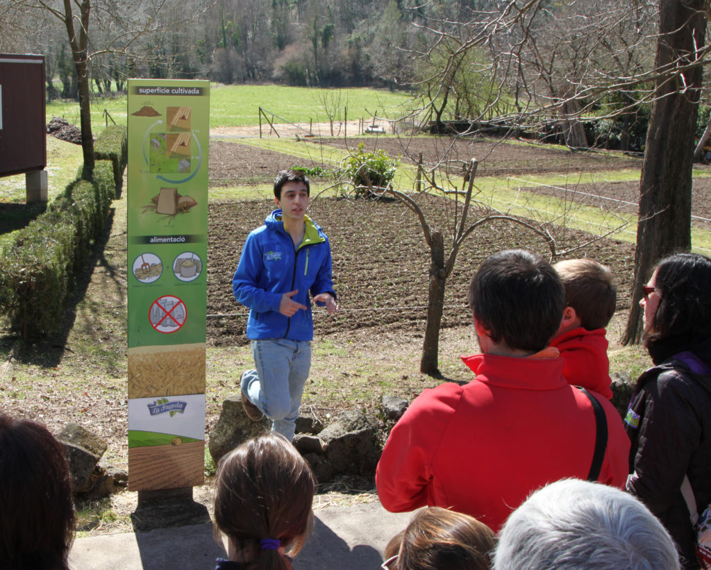 In a natural setting, in the outdoor gardens of La Fageda facilities, a boy speaks in front of a group of people who listen to him with interest. Image by La Fageda.