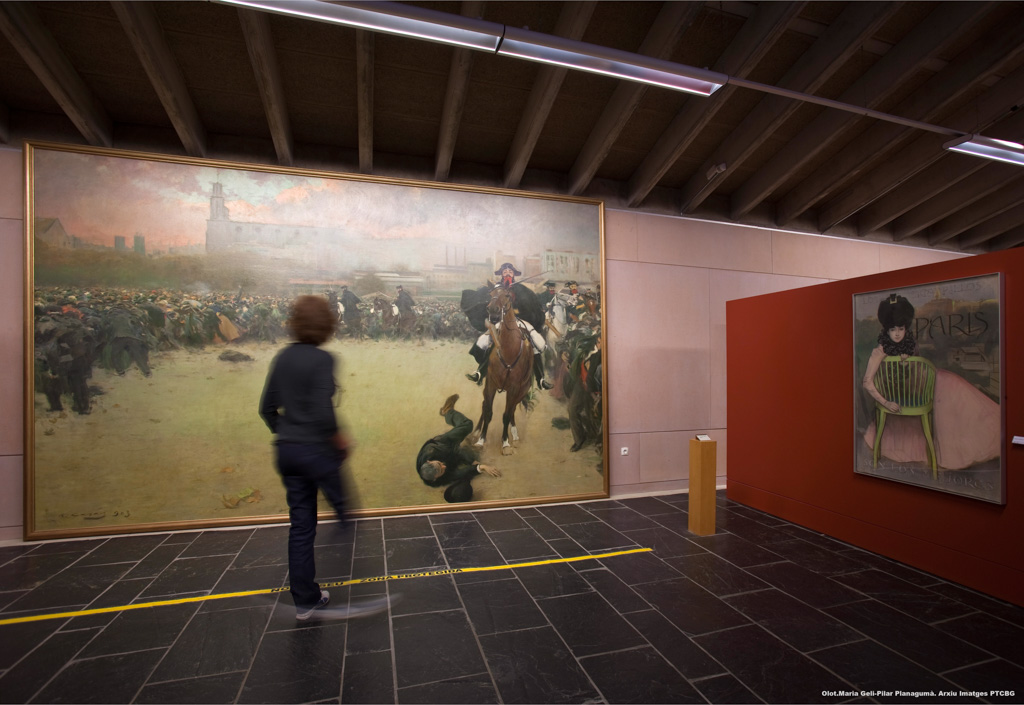 At the Museo de la Garrotxa, a woman observes the painting La Càrrega (The Charge), by Ramon Casas. On the right side of this large painting a civil guard on horseback runs over a demonstrator. On the left and in the background, a crowd runs away in terror. Image by Marina Geli and Pilar Planagumà.