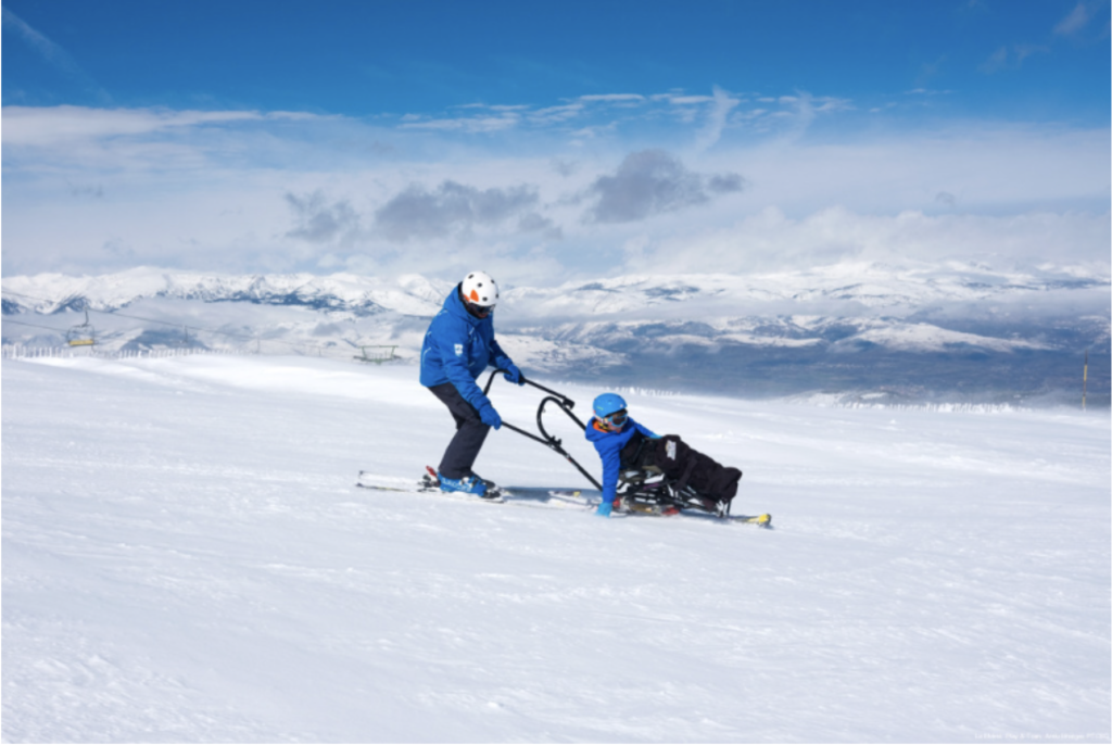 At La Molina ski resort, in a snowy alpine setting, a Play & Train skier pushes a user sitting in a ski chair. Image by Play and Train.