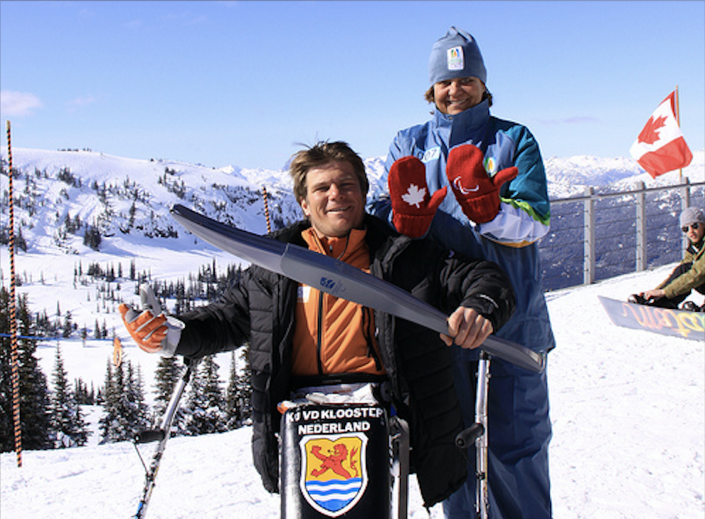 In a snowy alpine landscape, during the 2014 Vancouver Paralympics Games, Sylvana Mestre shares the Olympic torch with a Dutch athlete sitting in a ski chair. Image by Sylvana Mestre.
