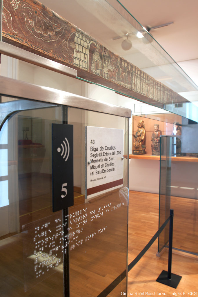 At the Museu d'Art de Girona, a Romanesque beam from the Benedictine monastery of Sant Miquel de Cruïlles is on display, decorated with a procession of clergymen. An information panel with text and Braille information stands below the piece. Image by Rafael Bosch.