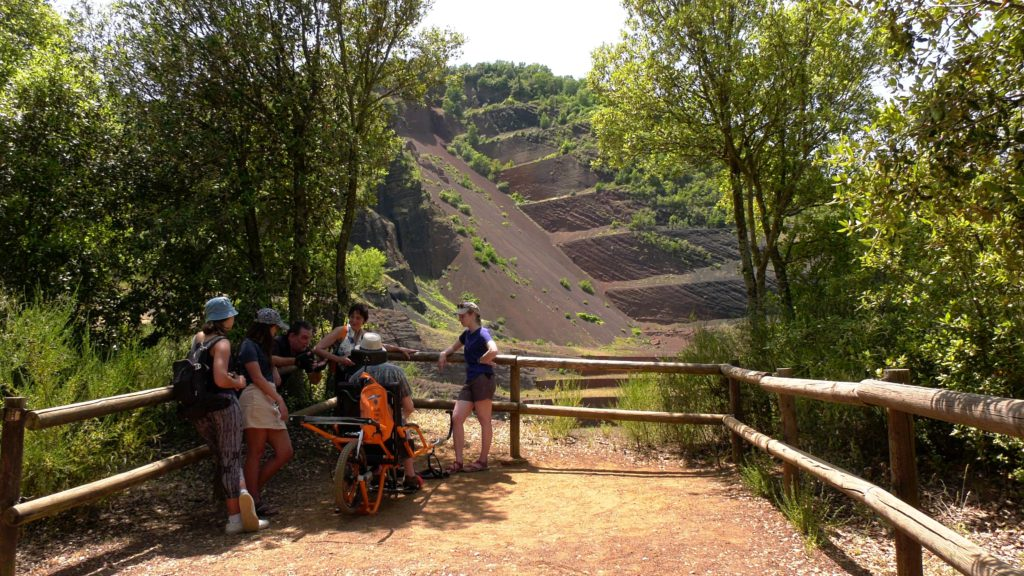 In front of the Croscat volcano, a family rests in the shade while contemplating the cut of the volcano, which allows to observe the inside of the cone, the chimney and the crater. One of the visitors is sitting on a Joëlette chair.  Image by MultiSignes.