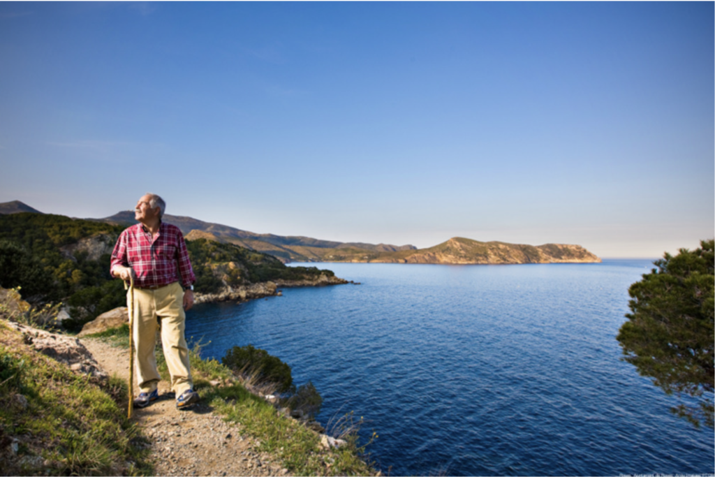 At Roses, on a path by the sea, a senior visitor walks around with a cane in his hand. As he walks, he contemplates the landscape, characterised by cliffs, myrtle and pine forests. Image by Roses Town Hall.