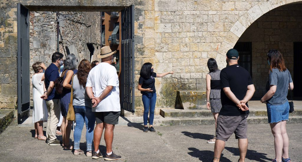 On a sunny day, a group of visitors and a guide listen to the explanations of the audio guide who describes a wall of yellowish tones made of irregular ashlars and with a semicircular vault. Image by MultiSignes.