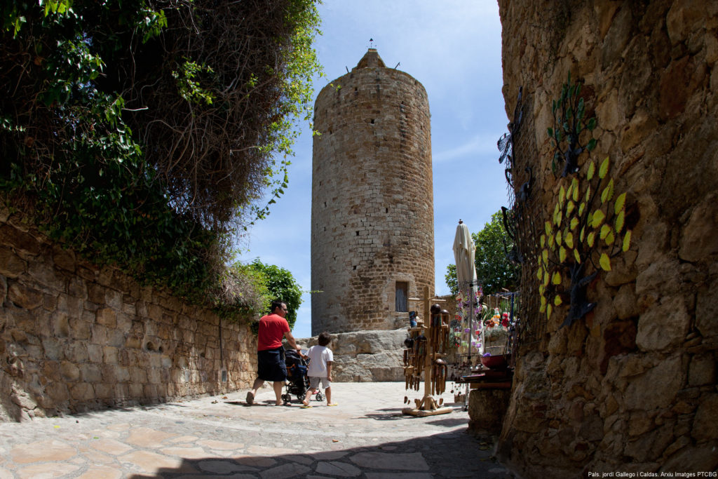 On a sunny day, a man pushing a pram walks along a cobbled street leading to the Torre de las Horas de Pals, a cylindrical construction about 15 metres high made of ashlars. Image by Jordi Gallego.
