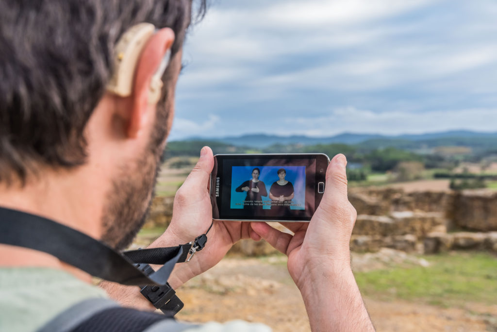 In Ullastret site, a man with a hearing aid attentively observes a descriptive video of the site through his mobile phone. On the screen, there are subtitles and a sign language interpreter. Picture of the Museu d'Arqueologia de Catalunya – Ullastret (@INMEDIA)