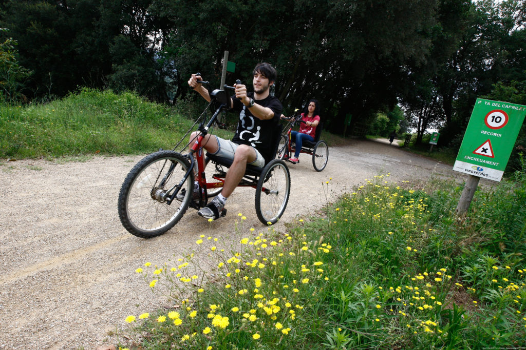 A boy and a girl drive a handbike through a greenway stretch. Alongside the path, on the grass, some yellow flowers flourish. Pere Duran's picture.
