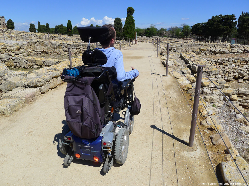 In the Greco-Roman archaeological site of Empúries, a man in a wheelchair advances along one of the paths of the itinerary. Image by Isabel Godoy.
