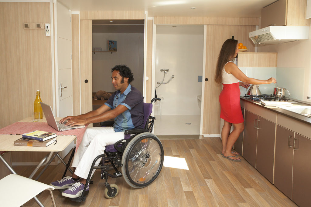 In the kitchen/dining room of an adapted bungalow at Valldaro Camping, a man in a wheelchair is typing on his laptop while a woman is cooking. Picture of Valldaro Campsite.