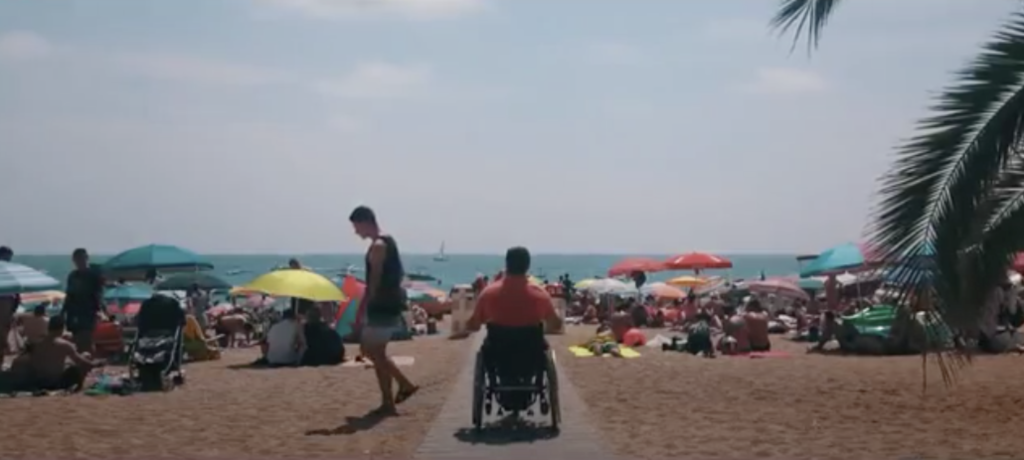 Two images from the video Acosta't. On the left, on the beach, the protagonist is in a wheelchair on an access ramp. On the right, he is sailing a small sailing boat.