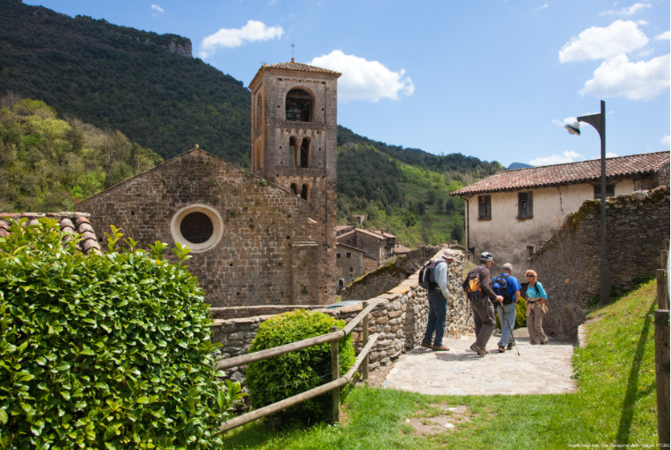 In Beget, a group of senior hikers walk along a cobbled path. In the background stands a Romanesque church made of ashlars, with a four-storey bell tower. Image by Maria Geli and Pilar Planagumà.