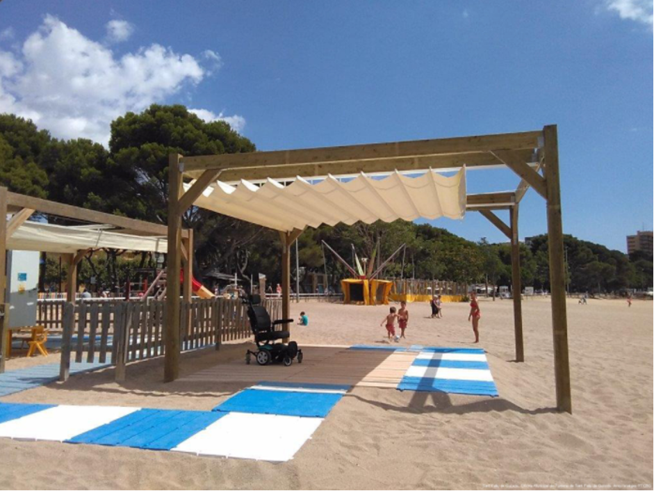 On the beach of Sant Feliu de Guíxols, an electric wheelchair rests under an accessible shaded area. Image by the Sant Feliu de Guíxols Municipal Tourist Office.