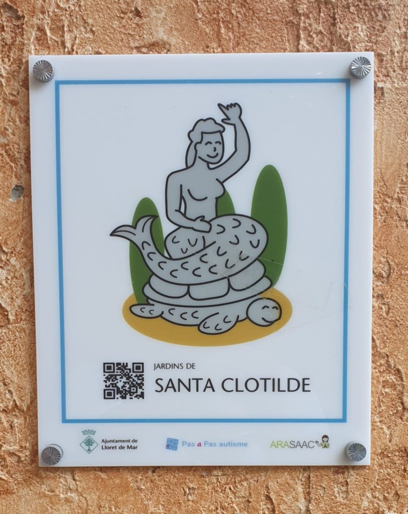 A detail of the pictogram indicating the Santa Clotilde Gardens. The pictogram depicts a mermaid sitting on the shell of a turtle. Picture by Lloret Turisme.